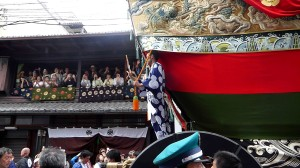 The Gion Festival's Ship Float is pulled past a traditional Kyoto townhouse.